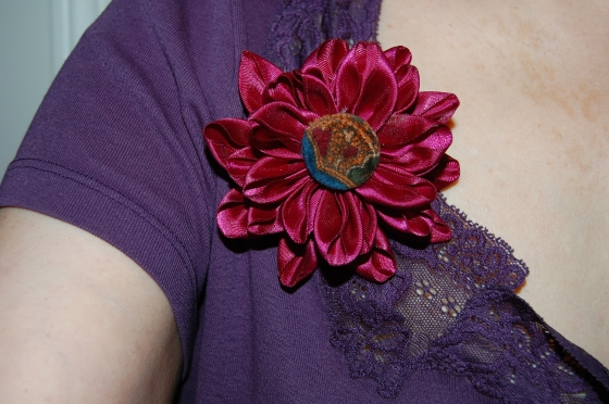first-attempt-kanzashi-flower-with-button-center-worn-on-purple